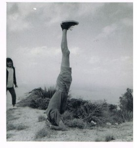 Man standing on his head on top a mountain